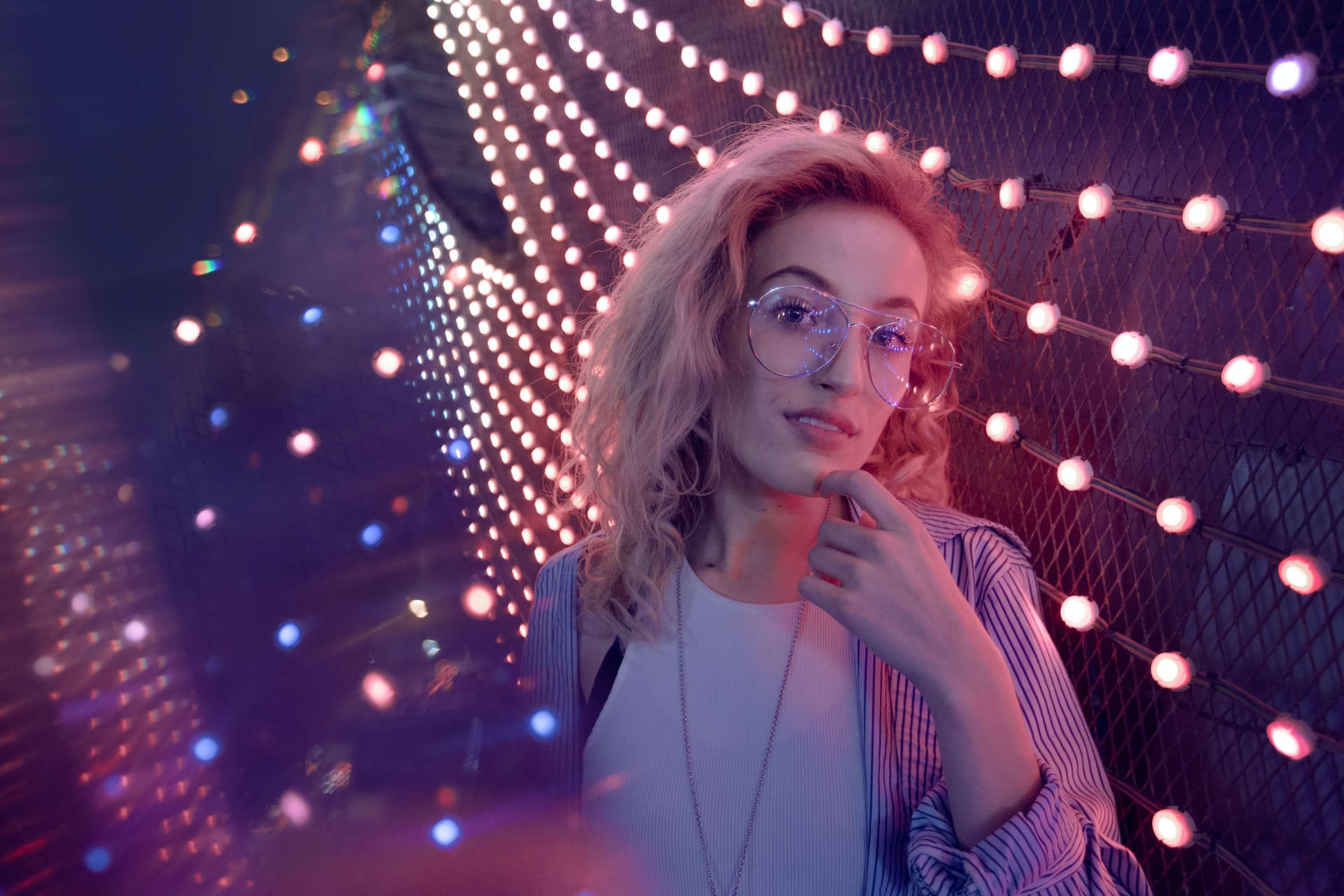 woman standing near string lights
