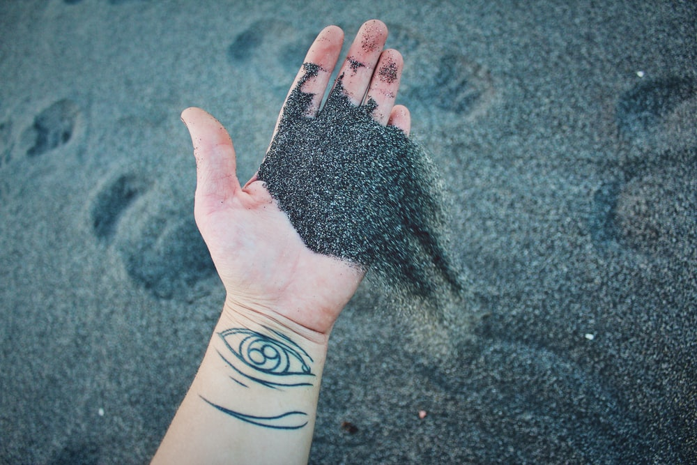 person holding gray sand