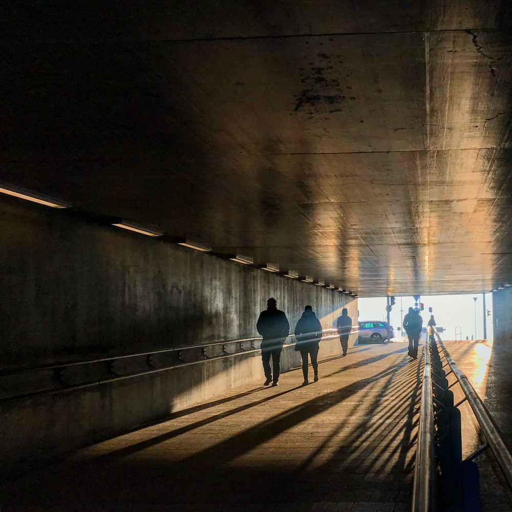 four people walking inside tunnel at daytime