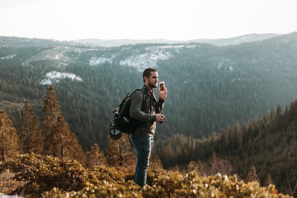 man wearing black jacket standing on mountain