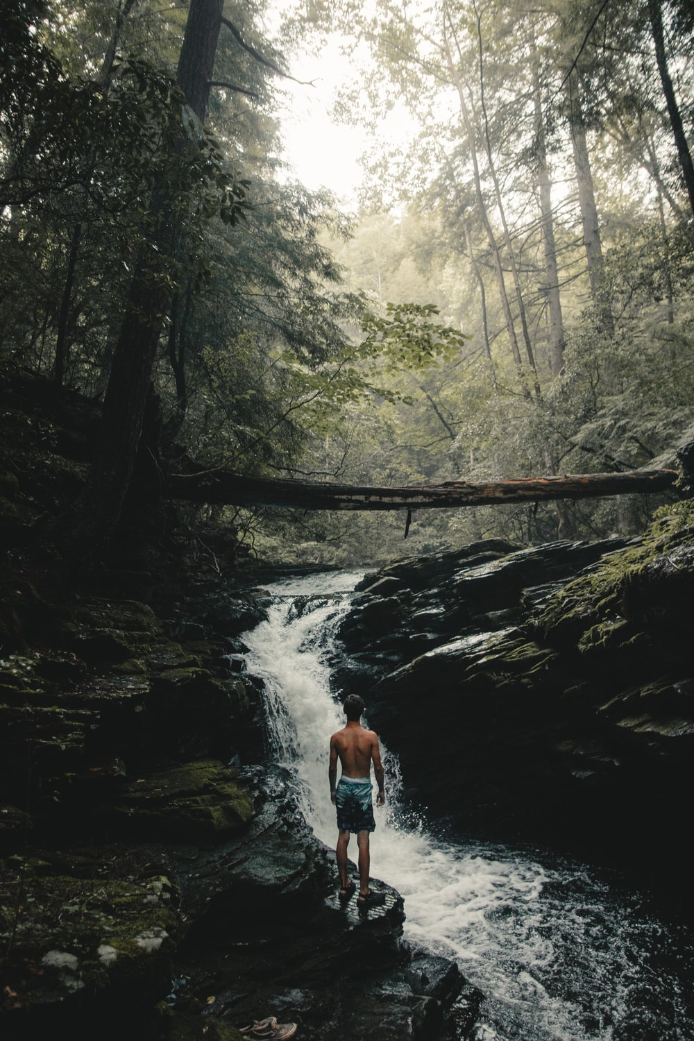 man wearing teal and black shorts standing beside waterfalls