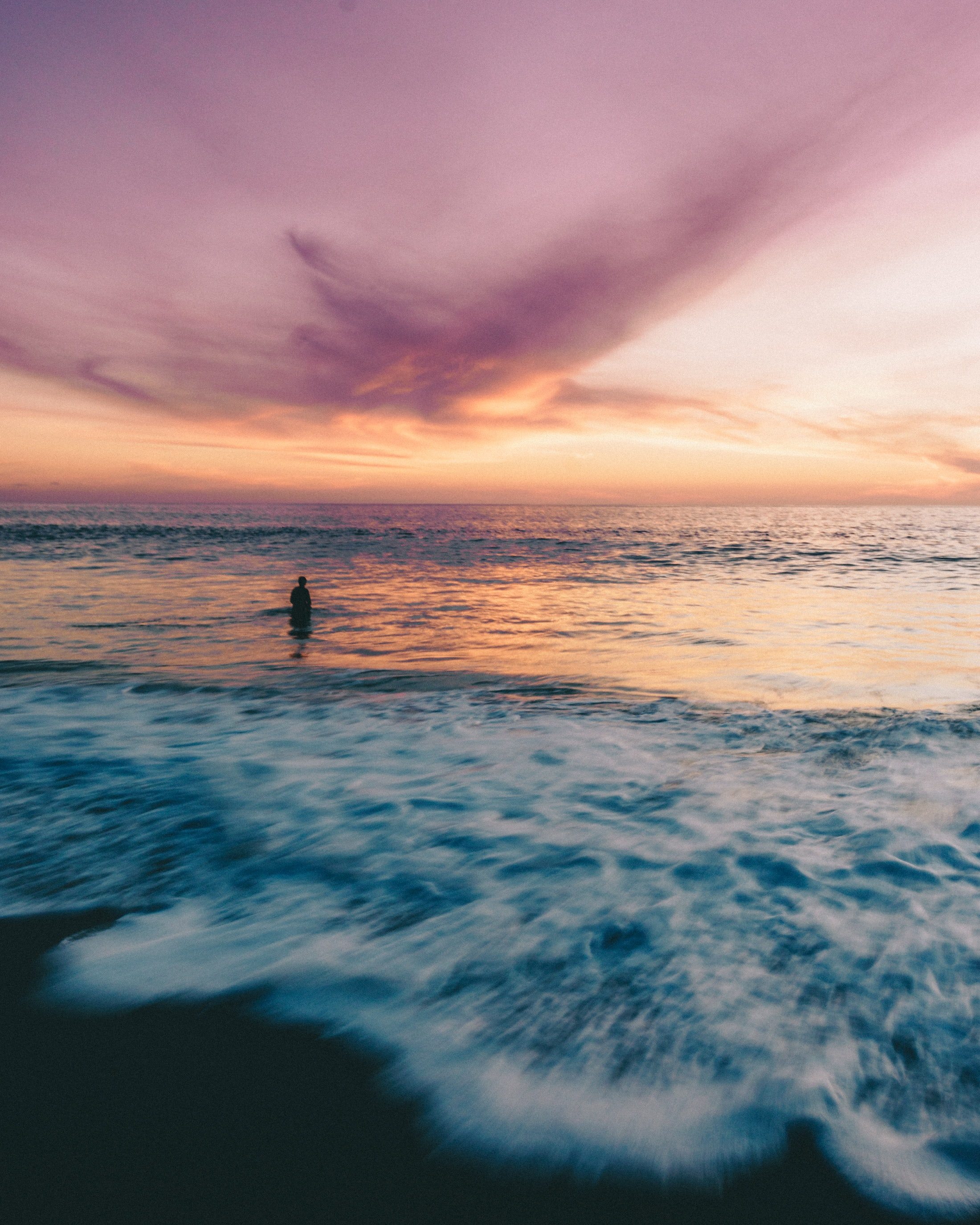 person standing on blue ocean water during orange sunset