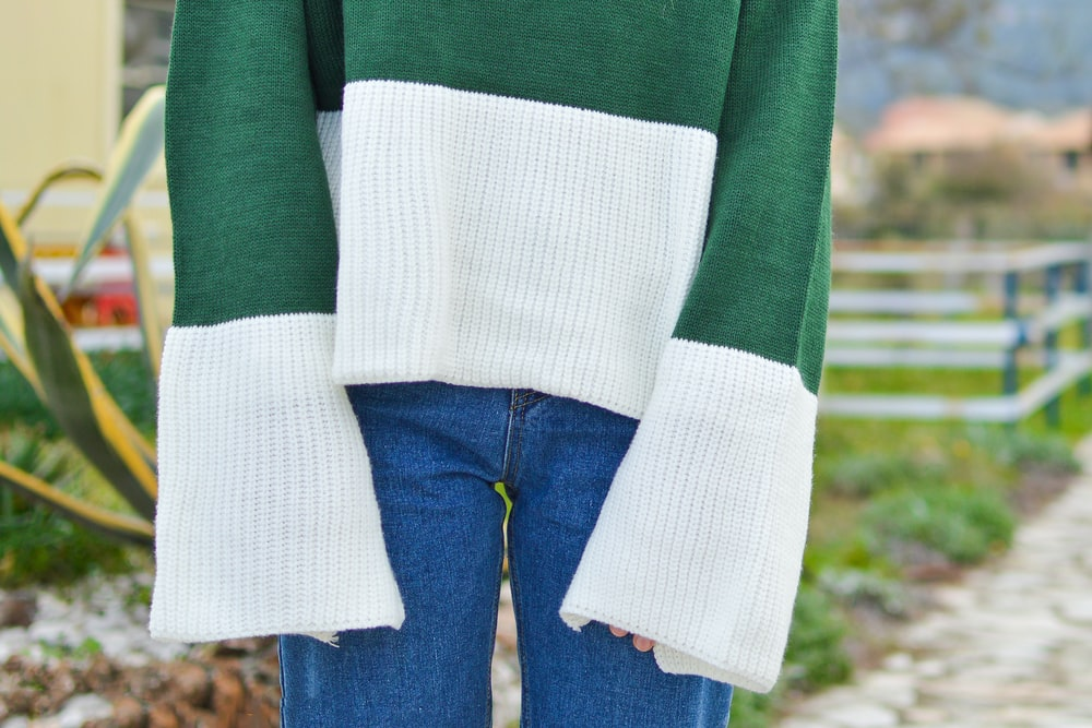 person wearing green and white long-sleeved top and blue denim bottoms