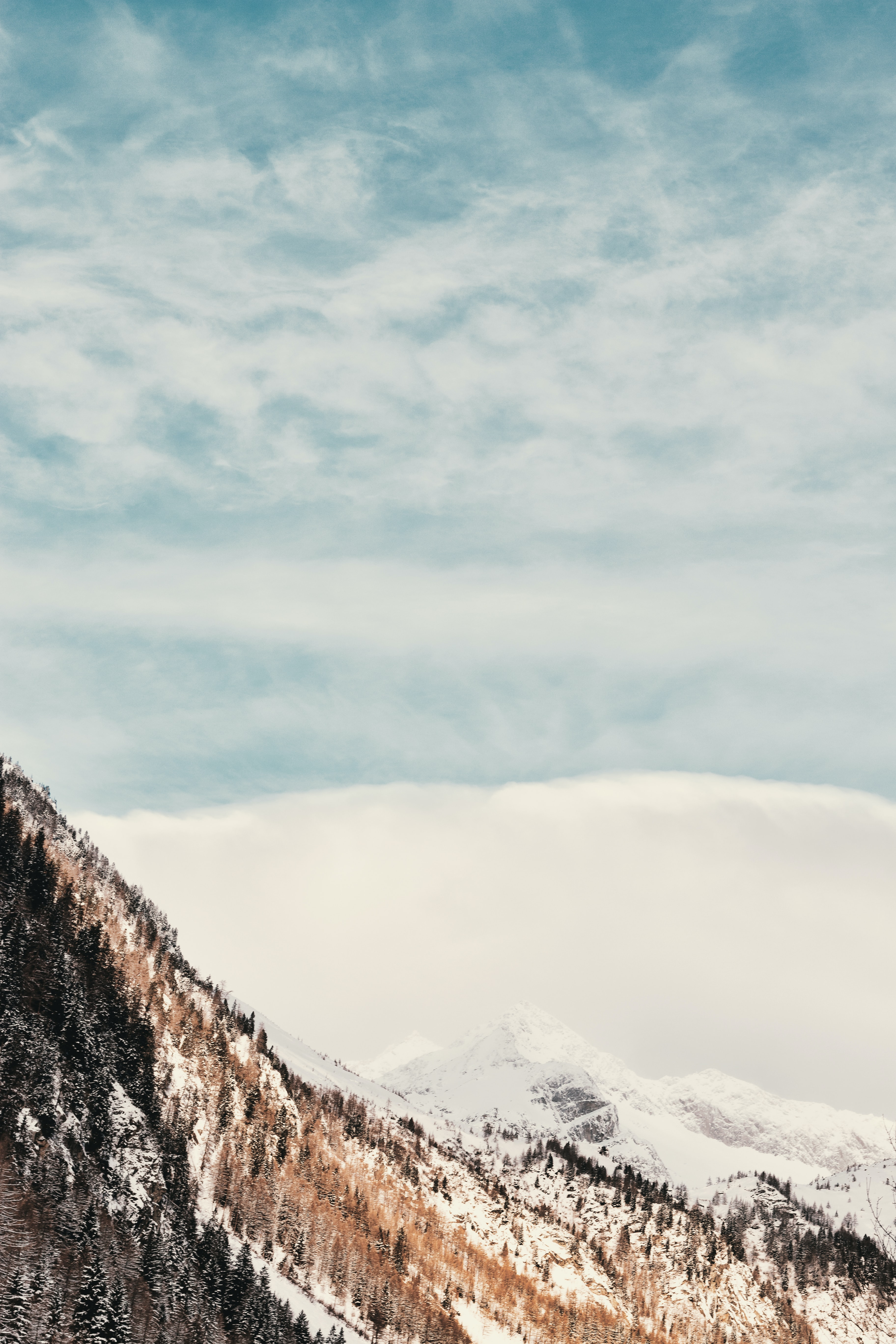 snowy mountain under cloudy sky