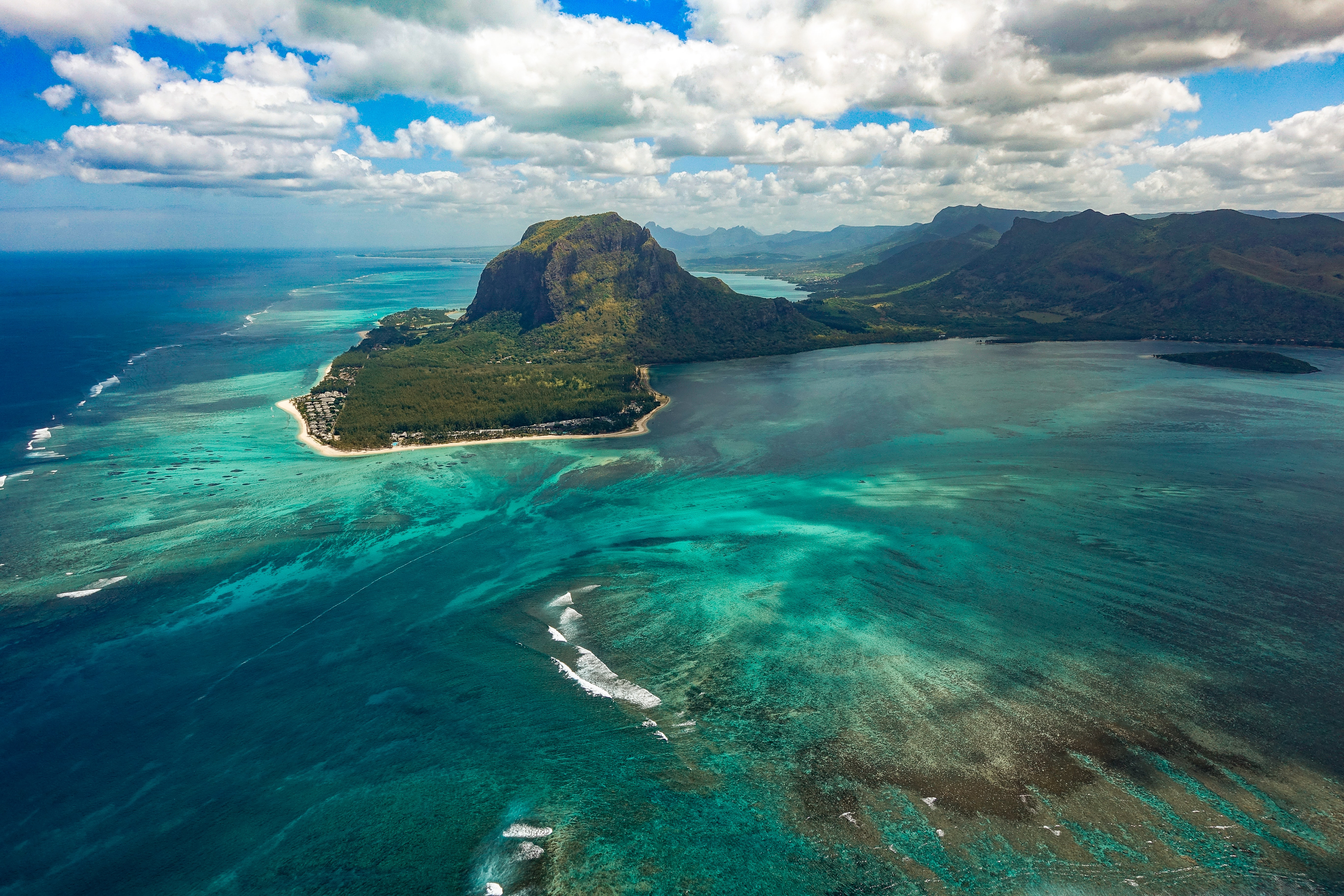 aerial photography of sea near mountain at daytime