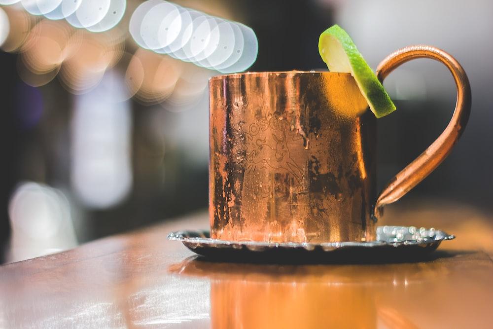 selective focus photo of brass-colored mug