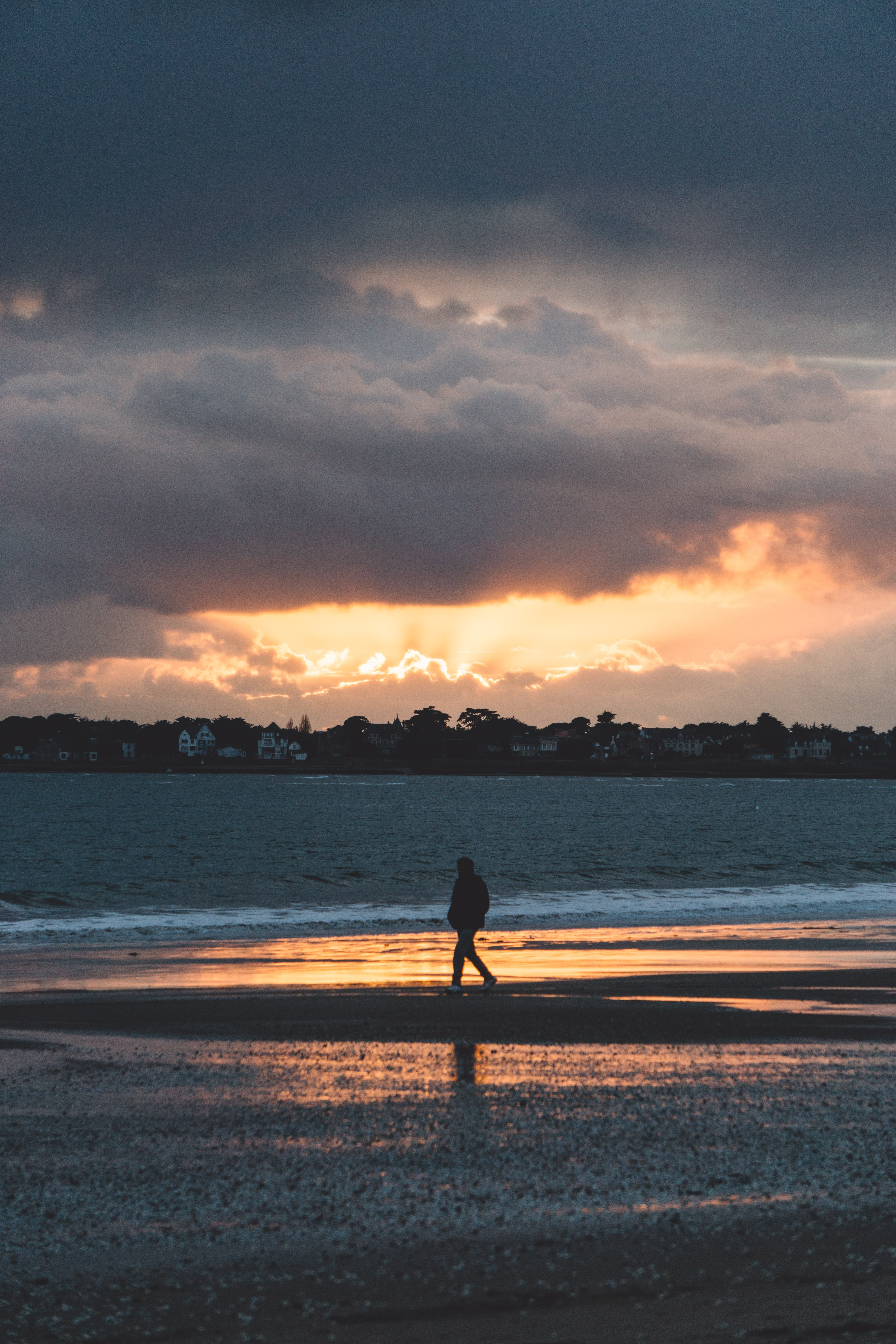 silhouette of person walking on the seashore