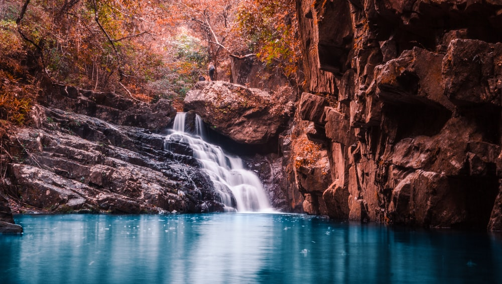 waterfalls surrounded by rocks during daytime