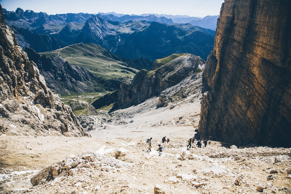 landscape photo of group of person walking on mountain