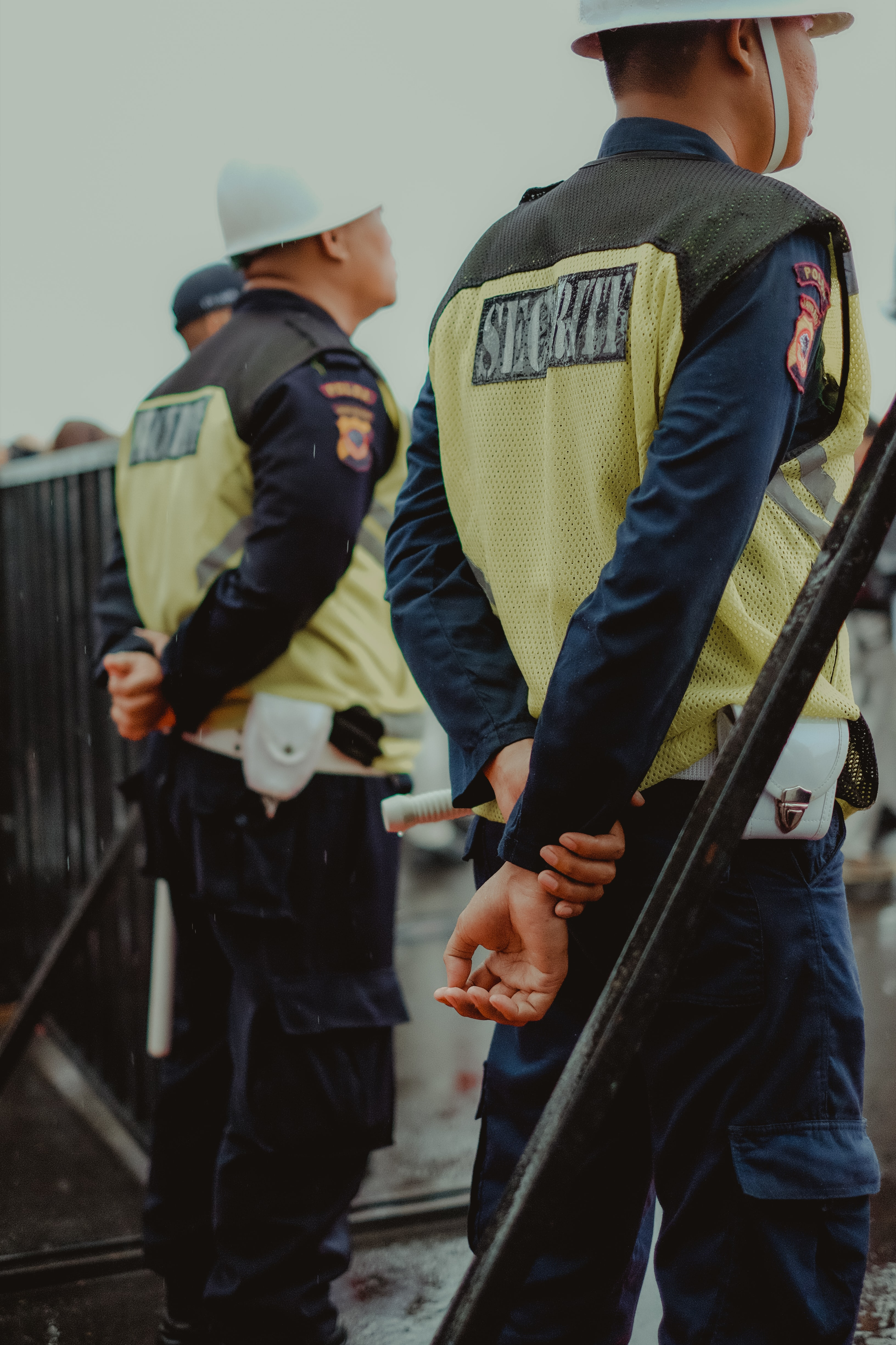policeman standing near black steel fence