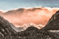 peach-colored cloud on top of mountain