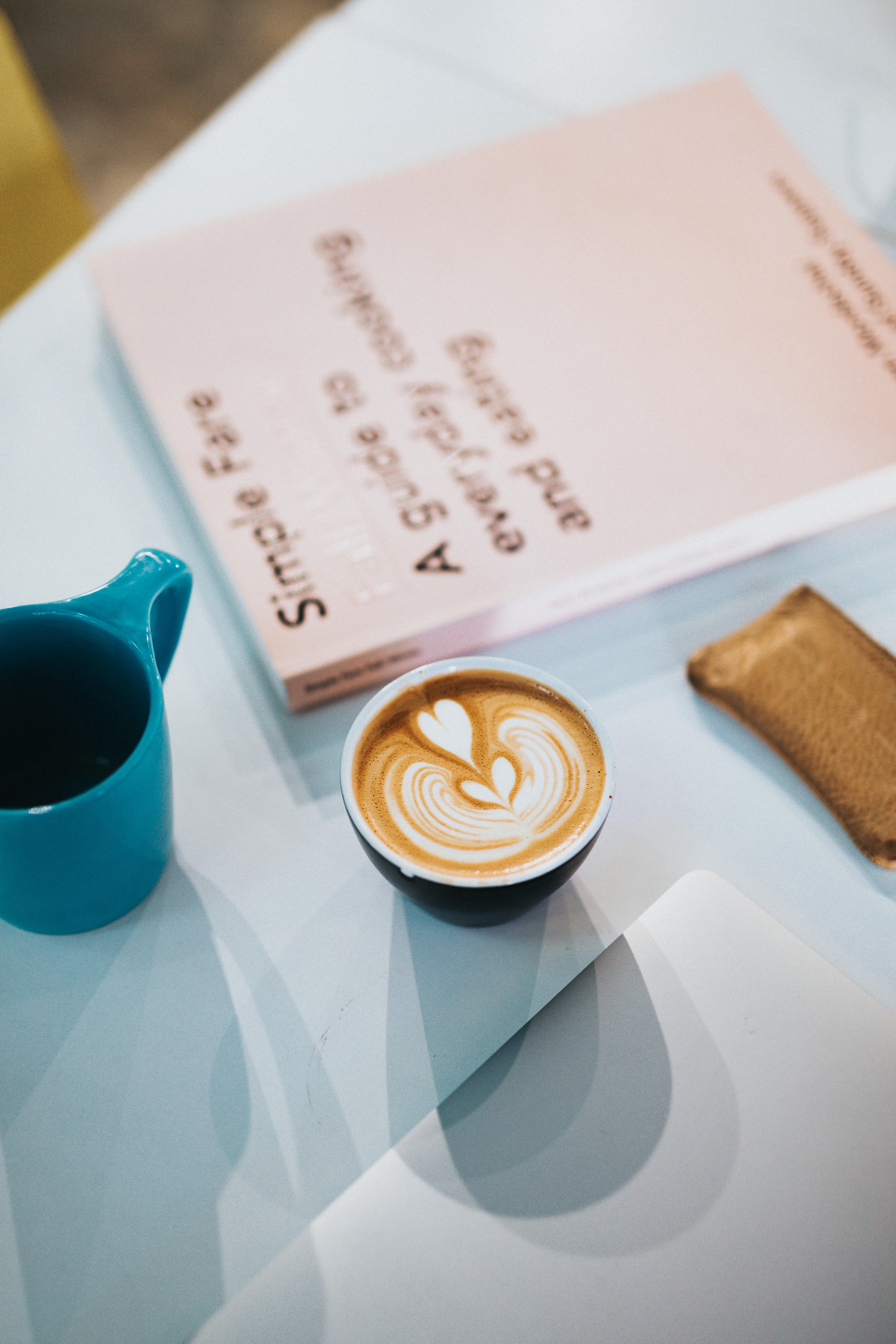 coffee filled ceramic mug beside book