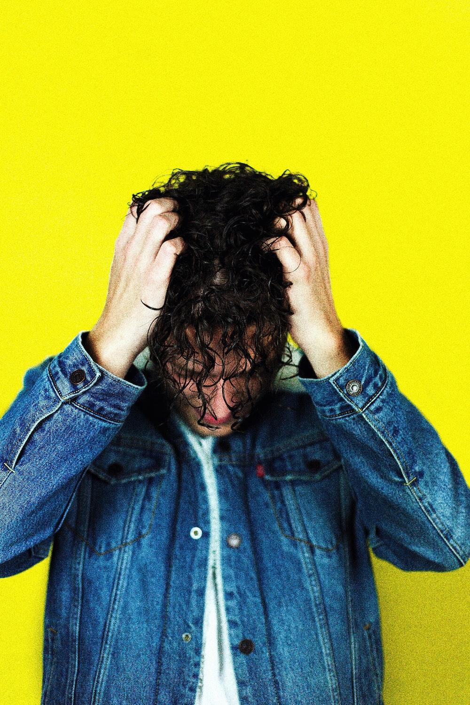 man in blue denim jacket holding his hair