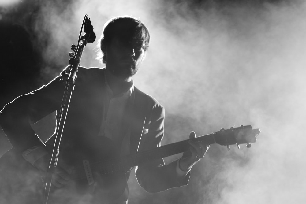 silhouette of man playing a guitar beside a microphone