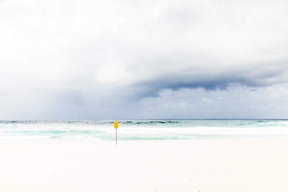 yellow pole on seashore under white clouds