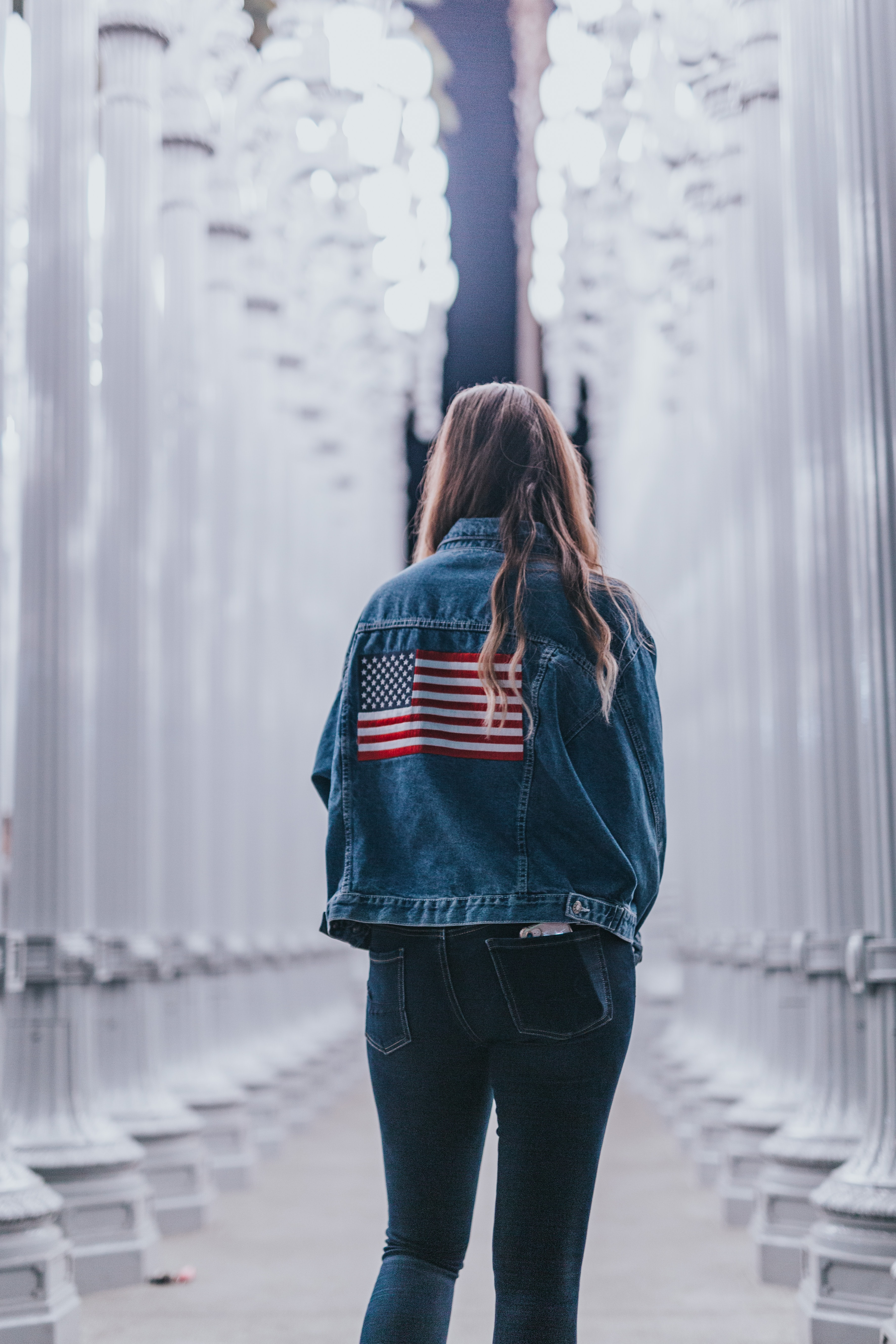 woman in blue denim jacket standing near pedestals