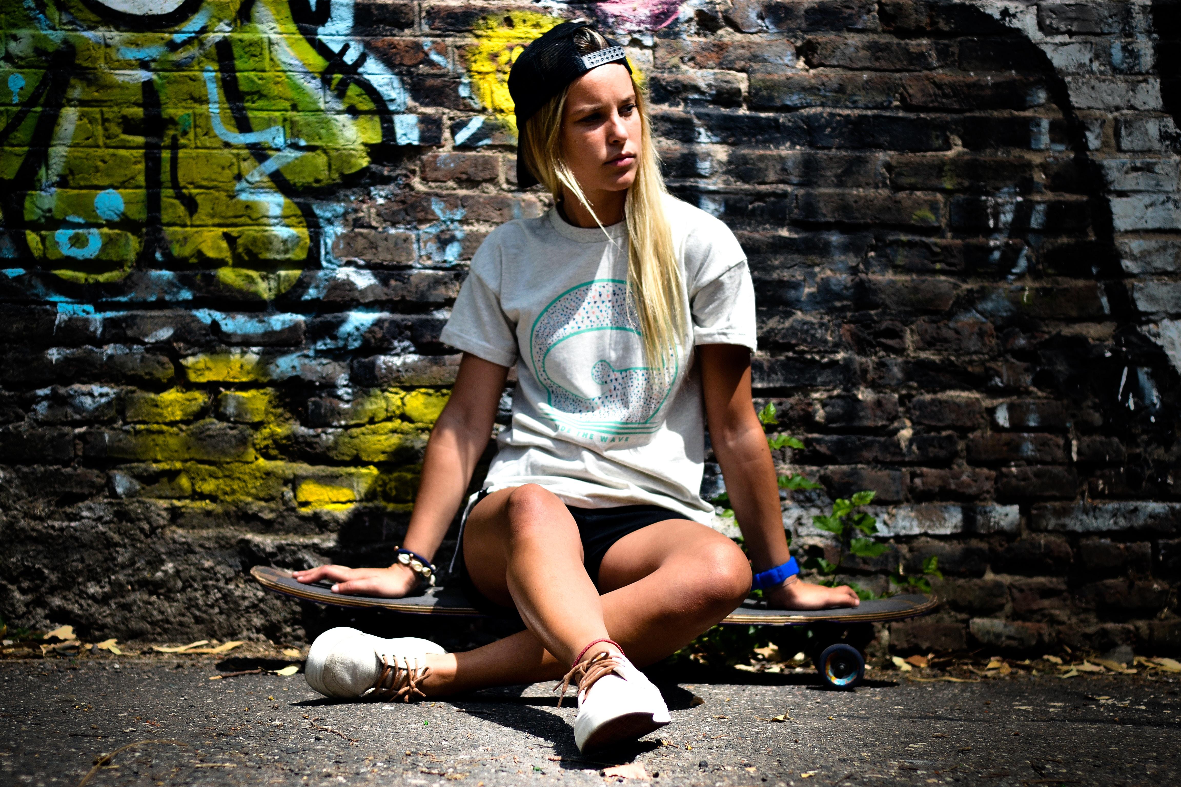 woman in white shirt sitting on skateboard