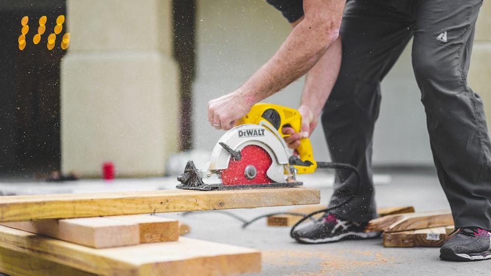 man in black sweatpants using DEWALT circular saw and cutting a wood plank