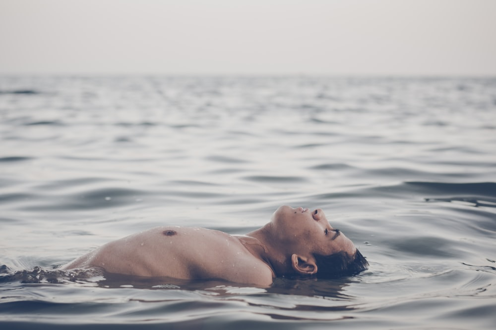 man floating on water during day