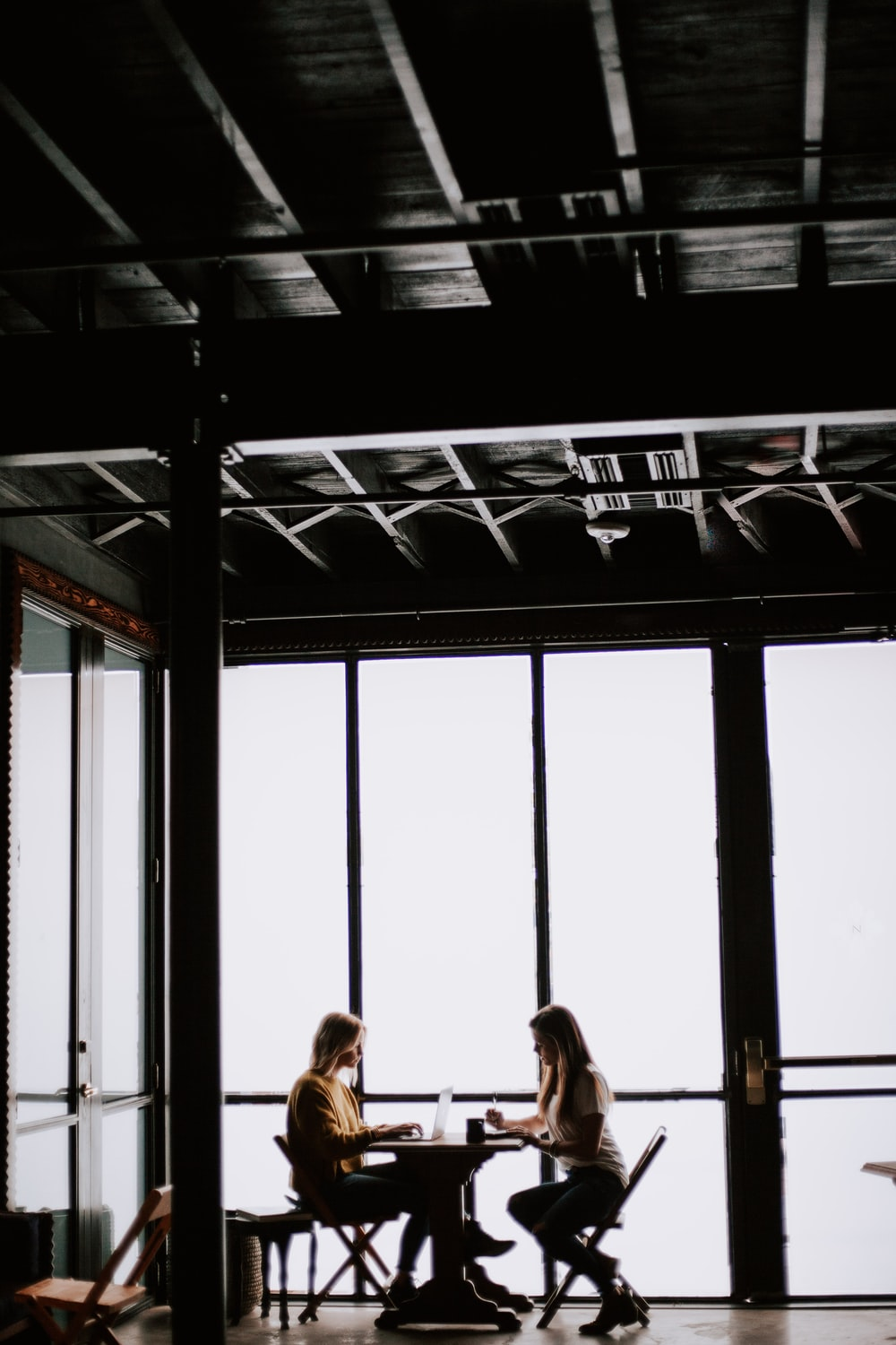 photo of two women facing each other sitting in front of table near glass wall
