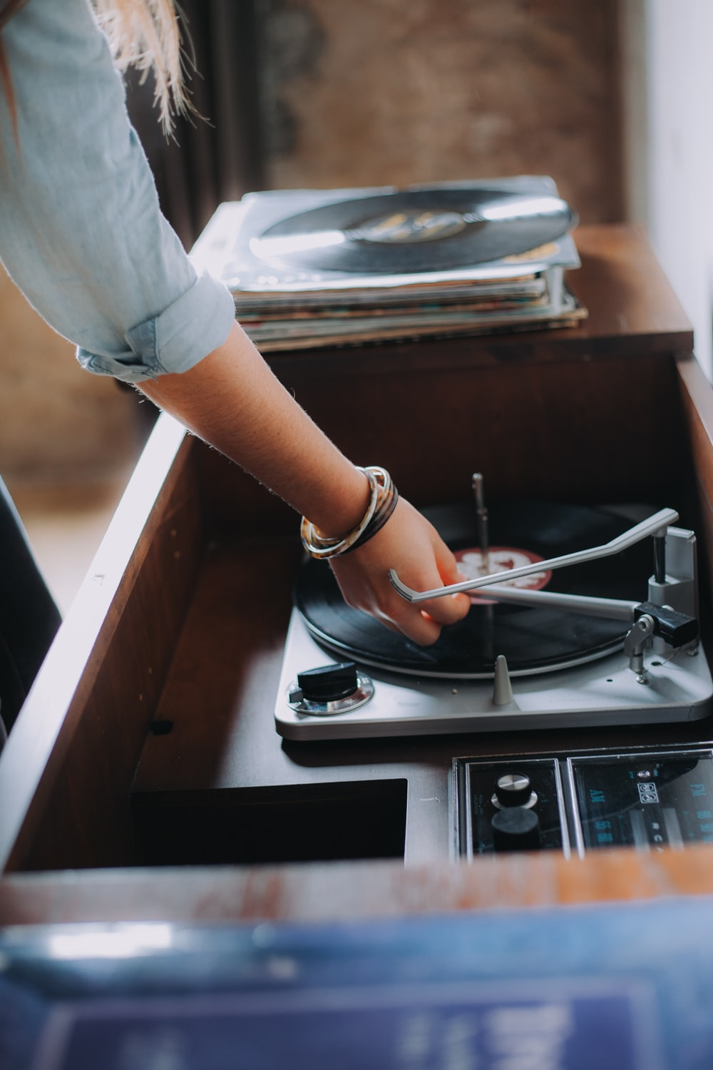 person holding gray and black vinyl record player