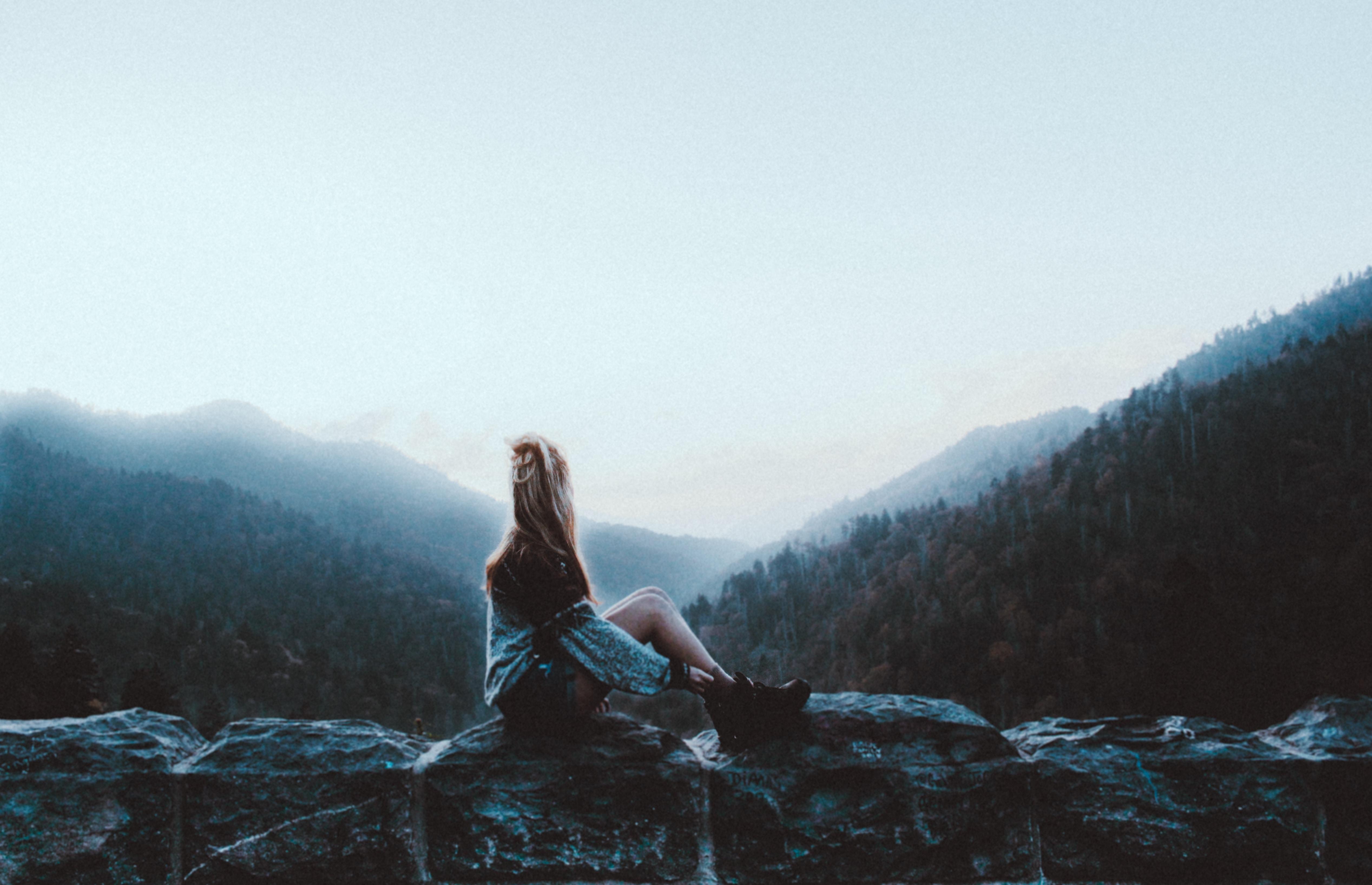 woman sitting on gray rock facing green mountains