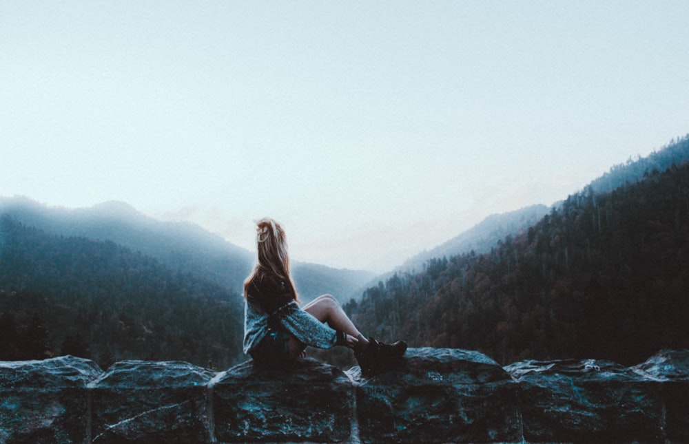 woman sitting on gray rock facing green mountains