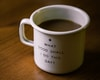 white and black ceramic cup filled with brown liquid on brown wooden sufface