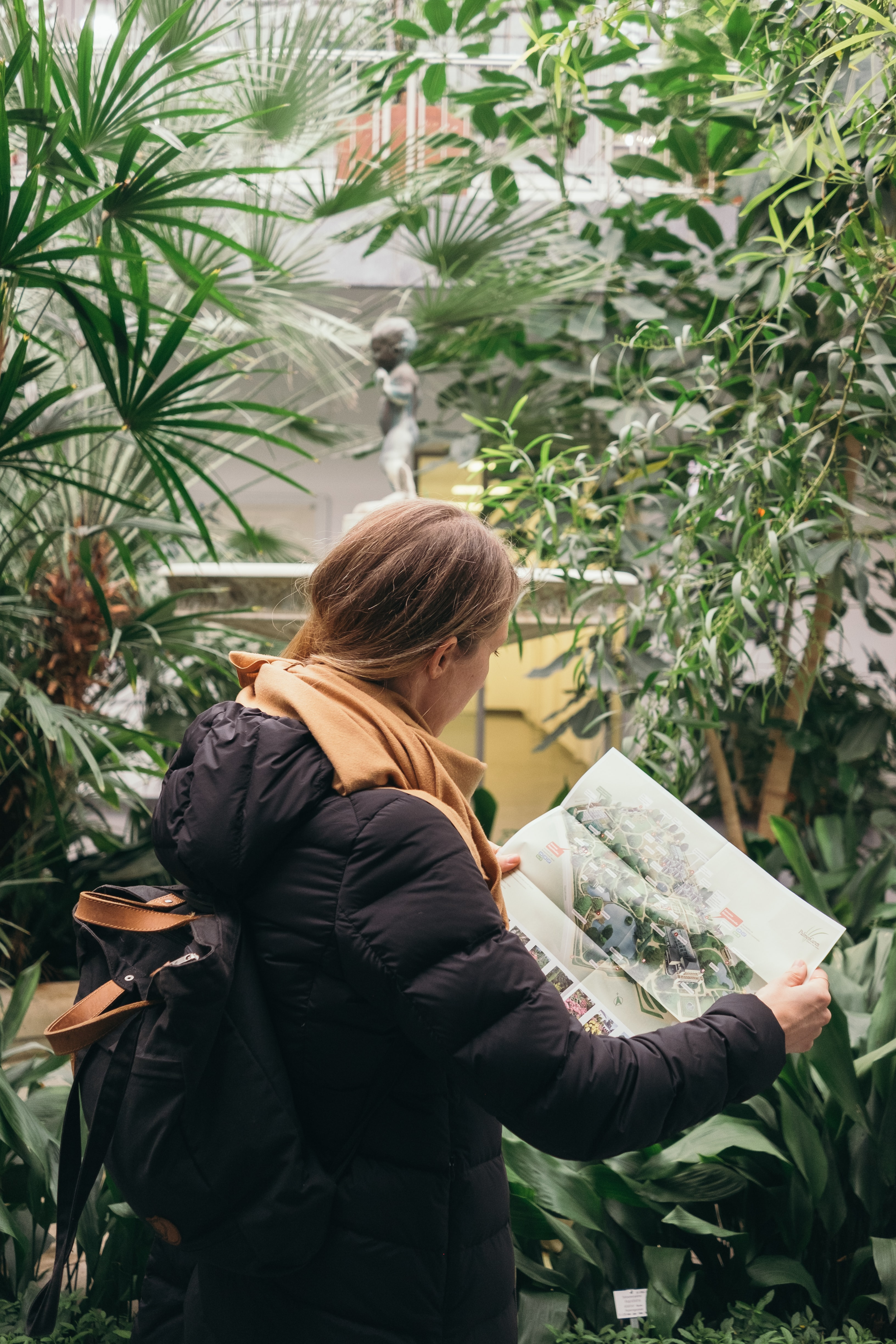 woman in black bubble hoodie holding map and surrounded by plants during daytime