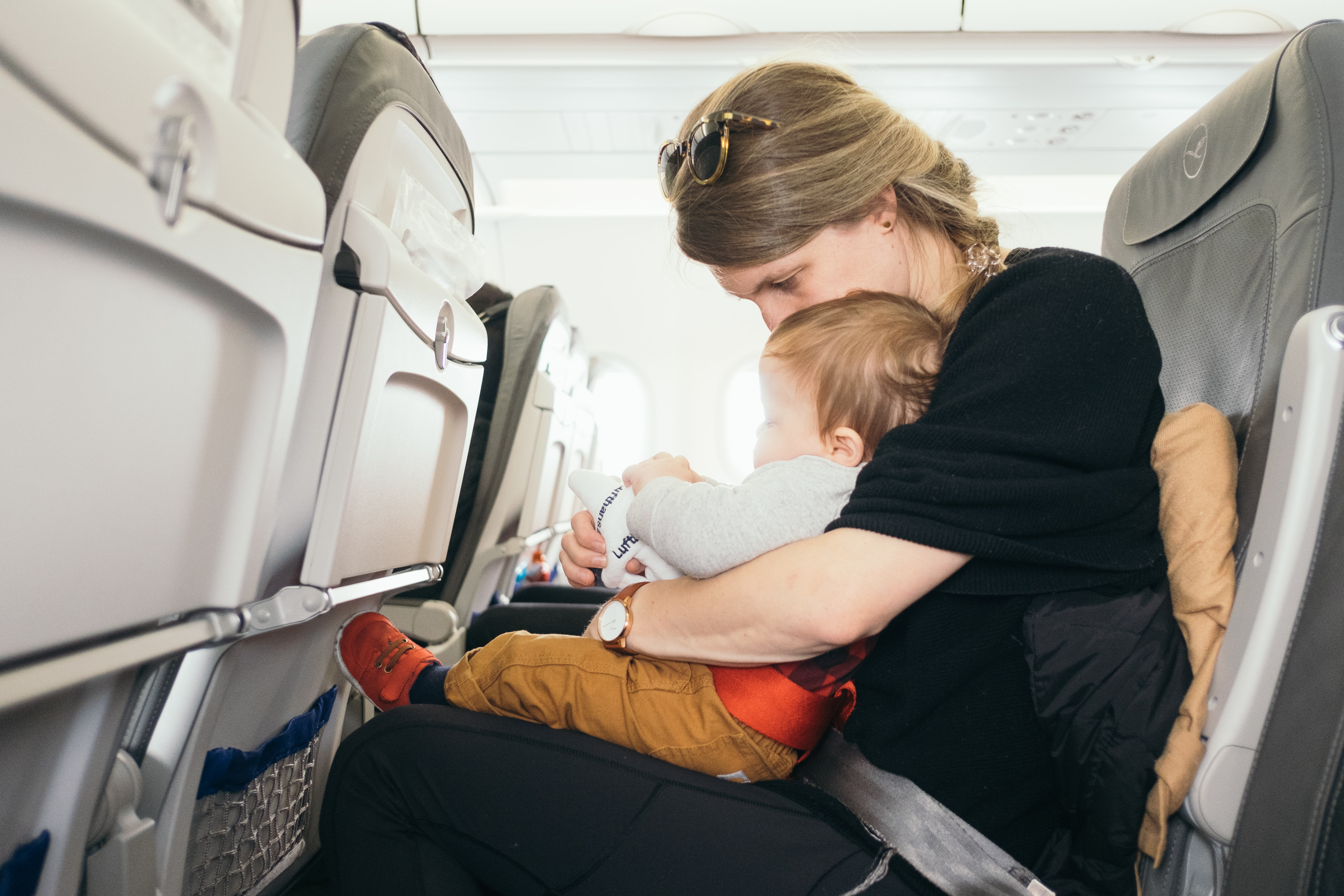 woman carrying baby while sitting on gray seat