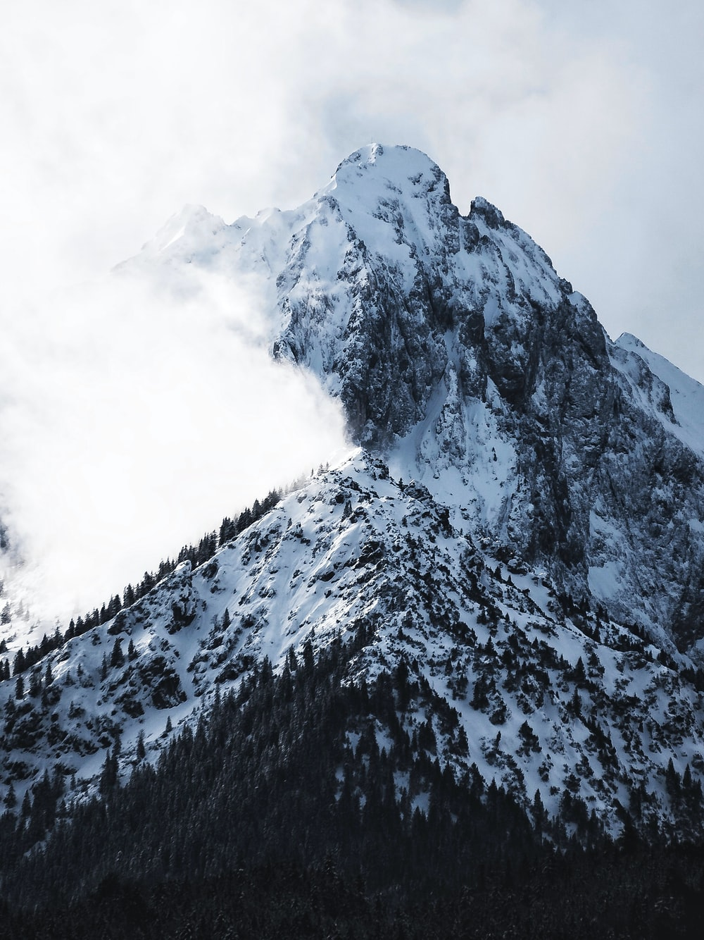 snowy mountain covered with clouds