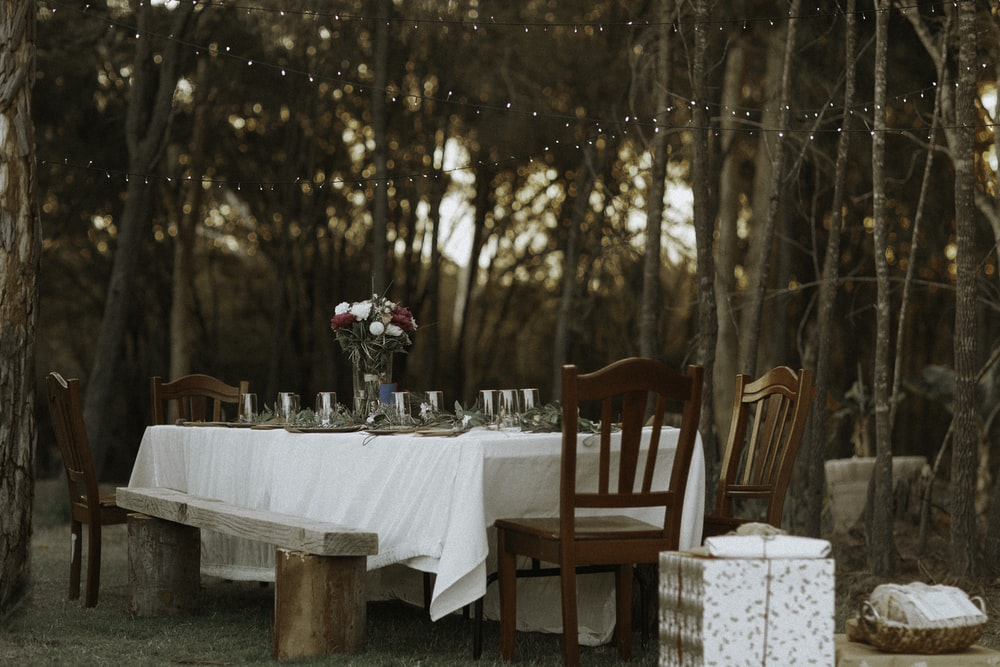 dining table and chairs set in the middle of the woods