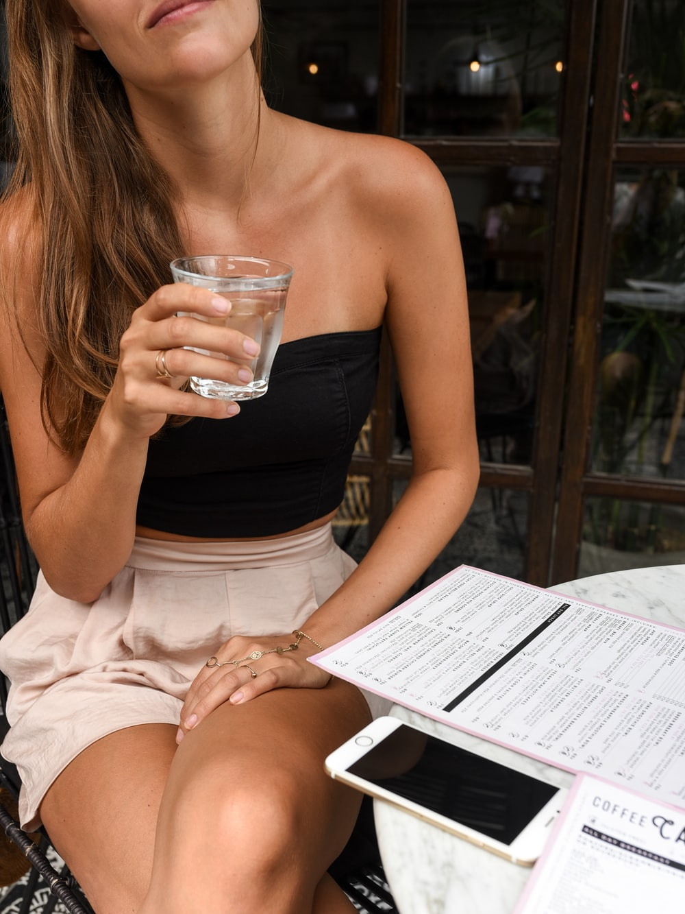 woman in black crop top holding clear rock glass