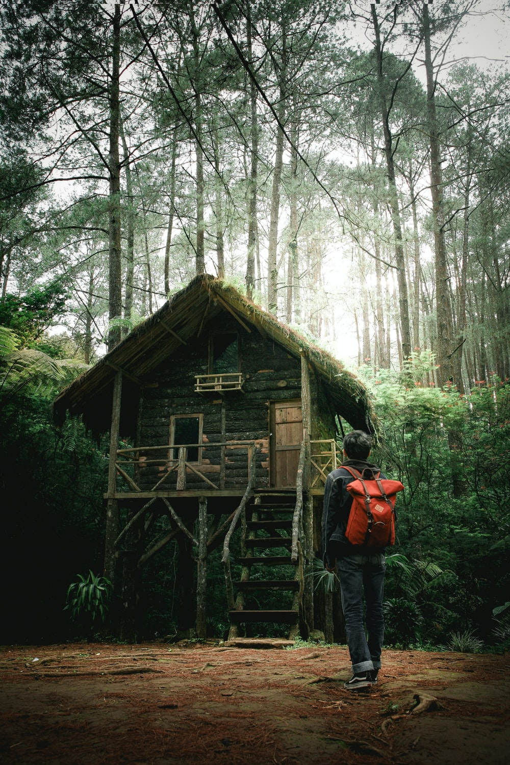 man with backpack beside a wooden house at the forest