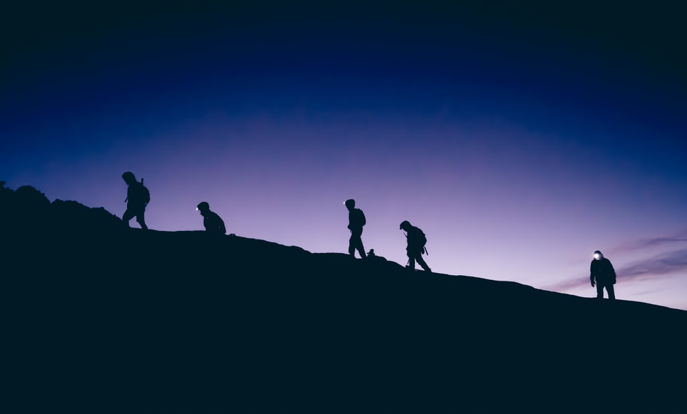 silhouette of five persons walking on hill