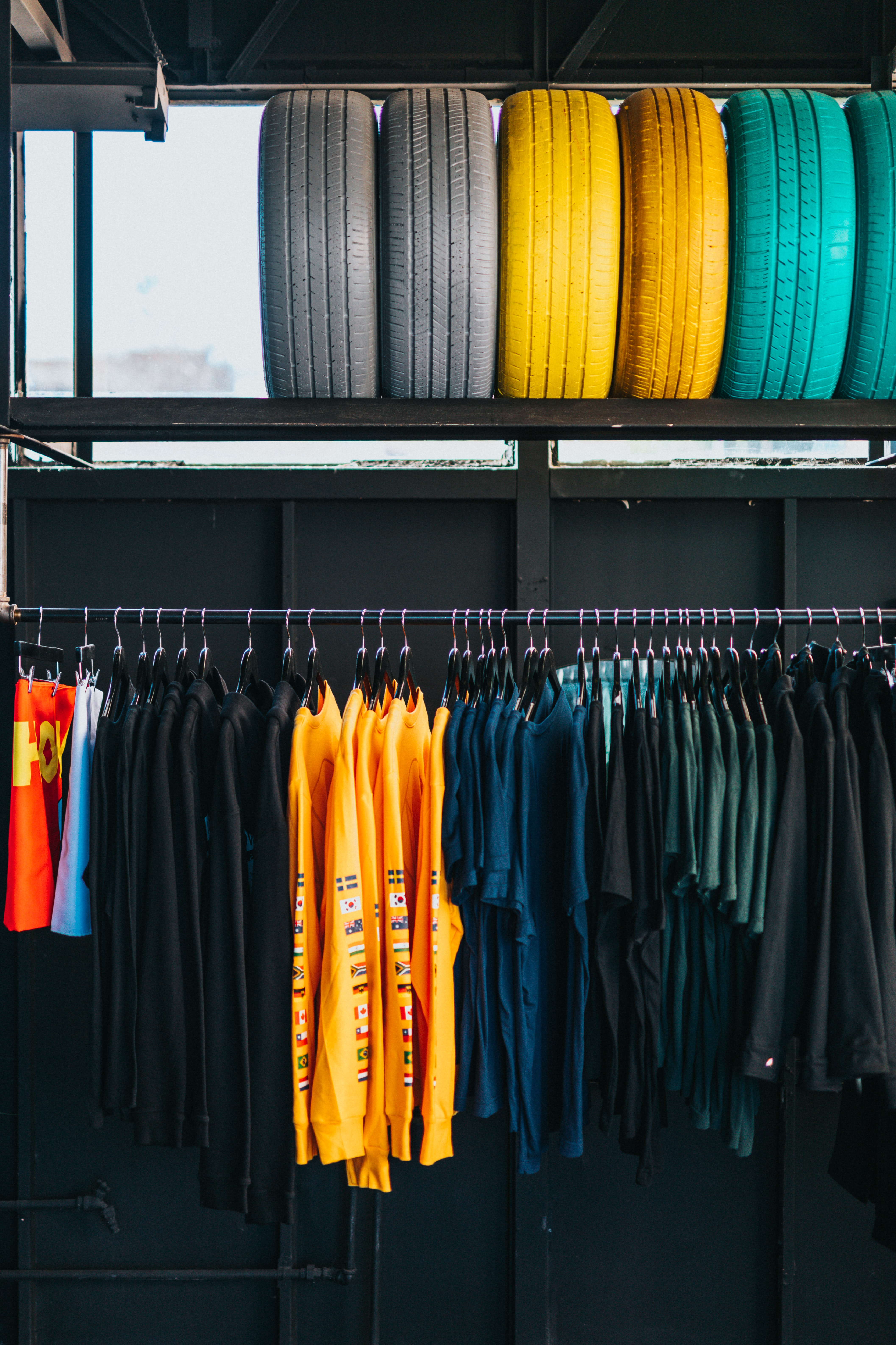 assorted-color clothes hanged on rack below six assorted-color ties