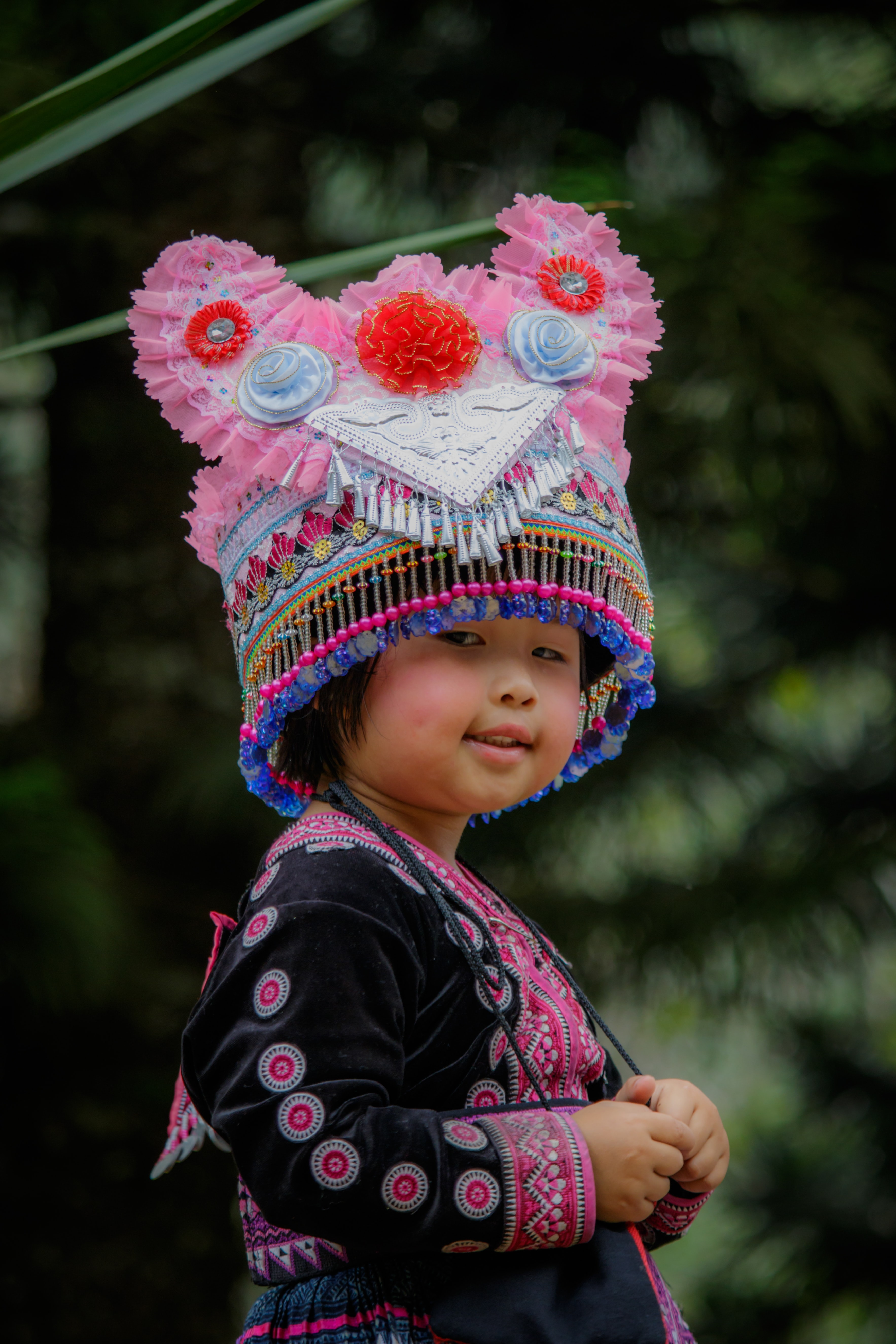 toddler wearing pink and blue beaded tassel hat