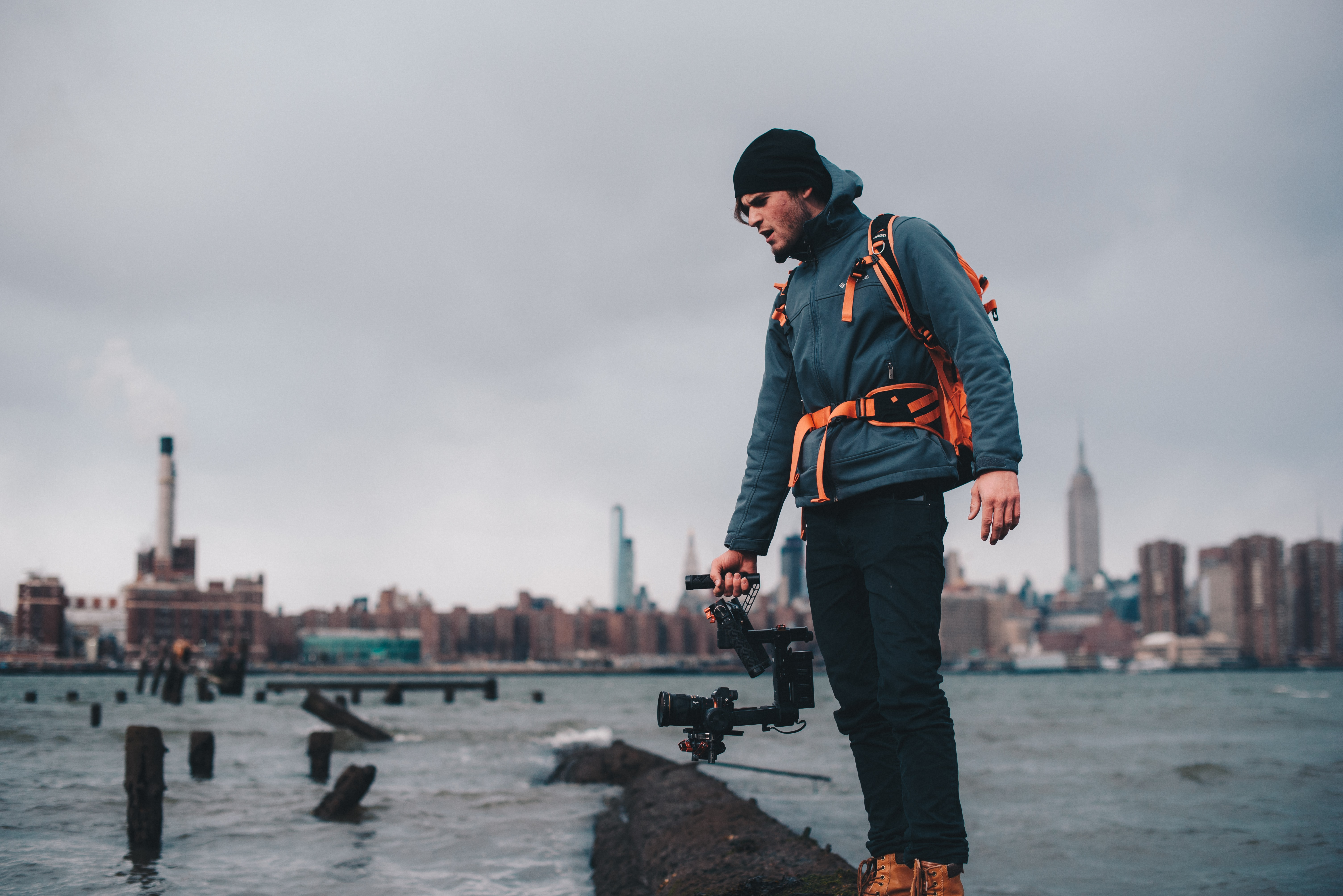 man wearing teal zip-up bubble jacket taking photo of body of water with camera with stabilizer