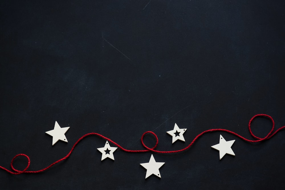 white stars cutout on black surface with red string