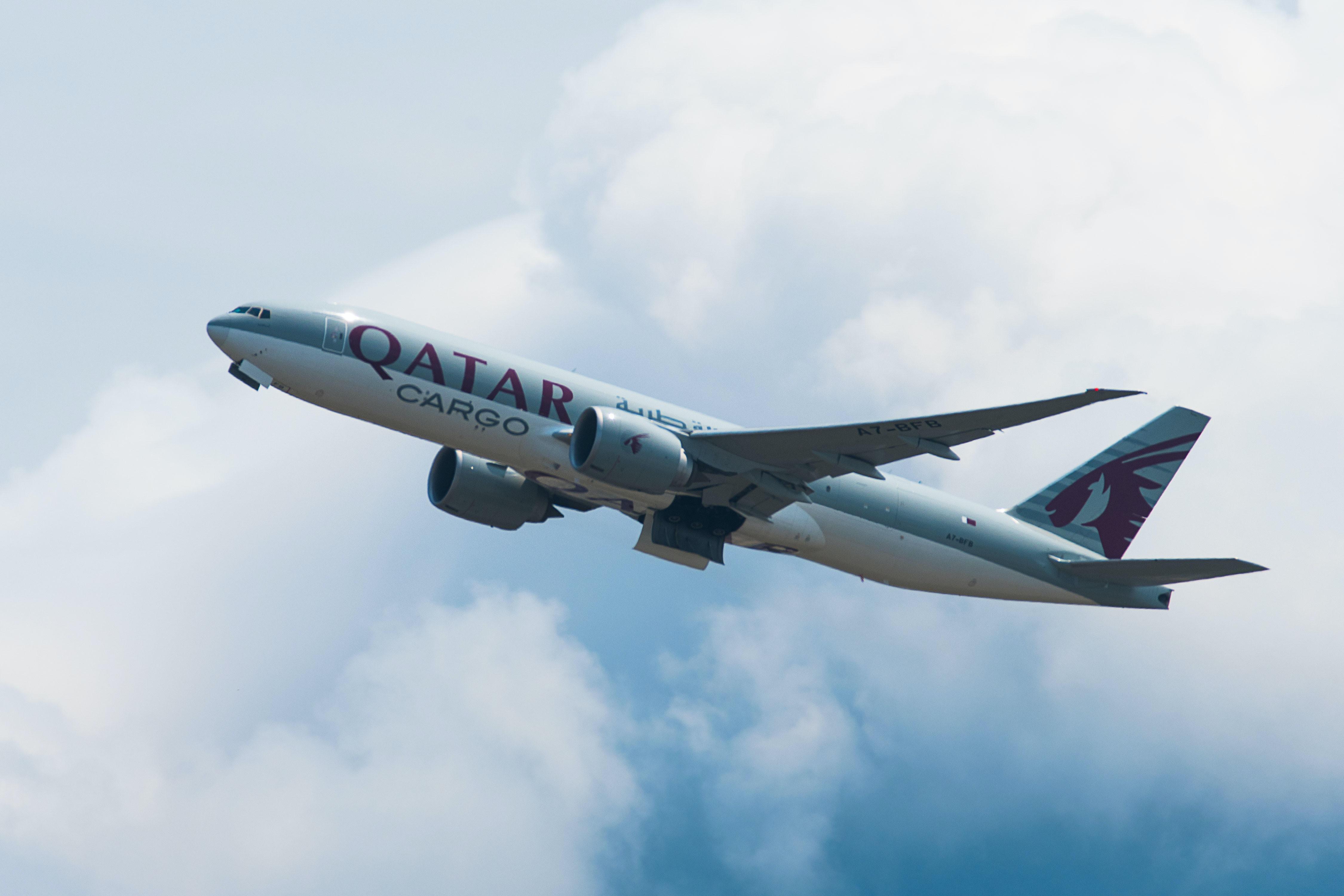gray and white Qatar Cargo plane on mid sky taken under white cloudy sky taken at daytime