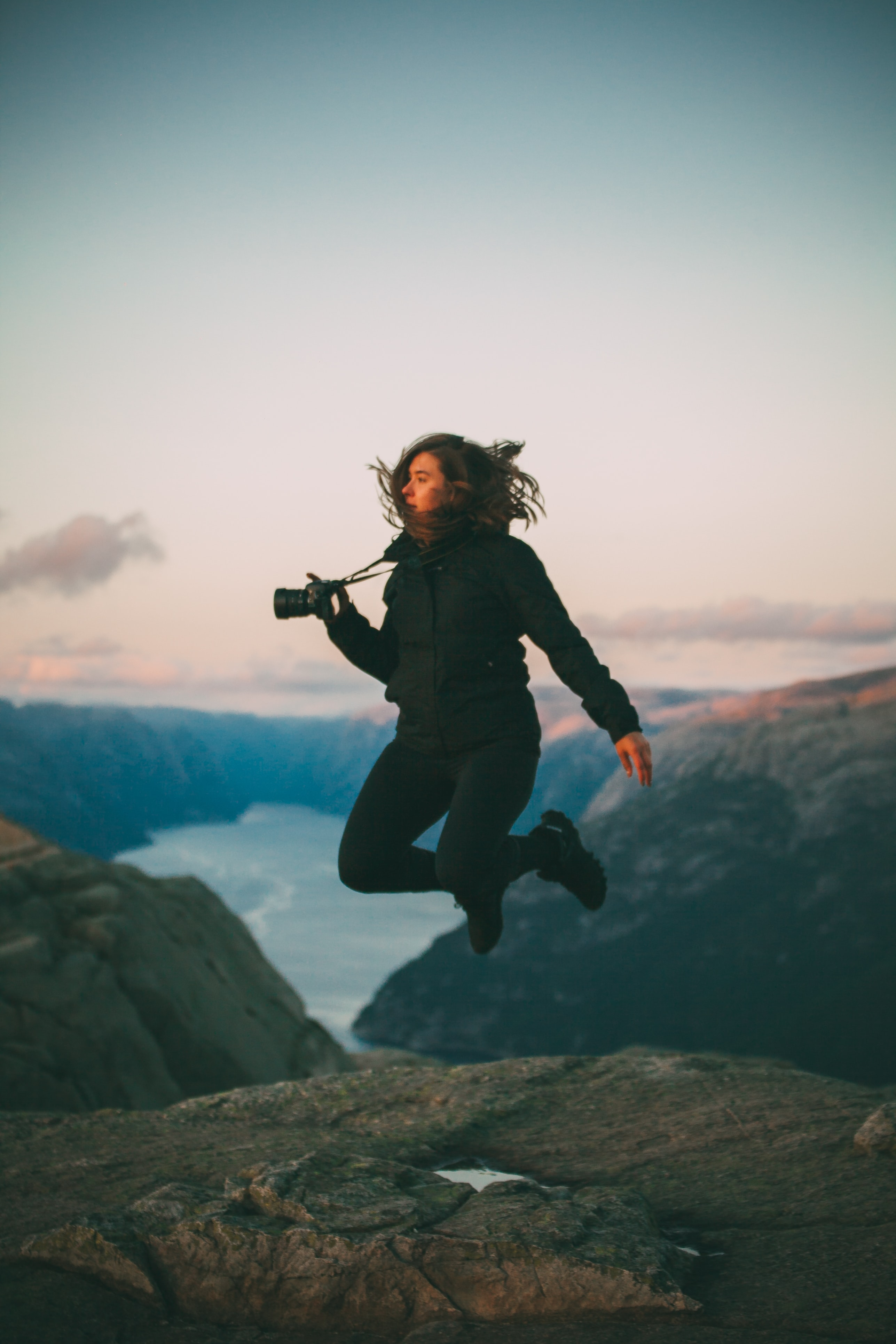 selective focus photo of woman jumping holding camera