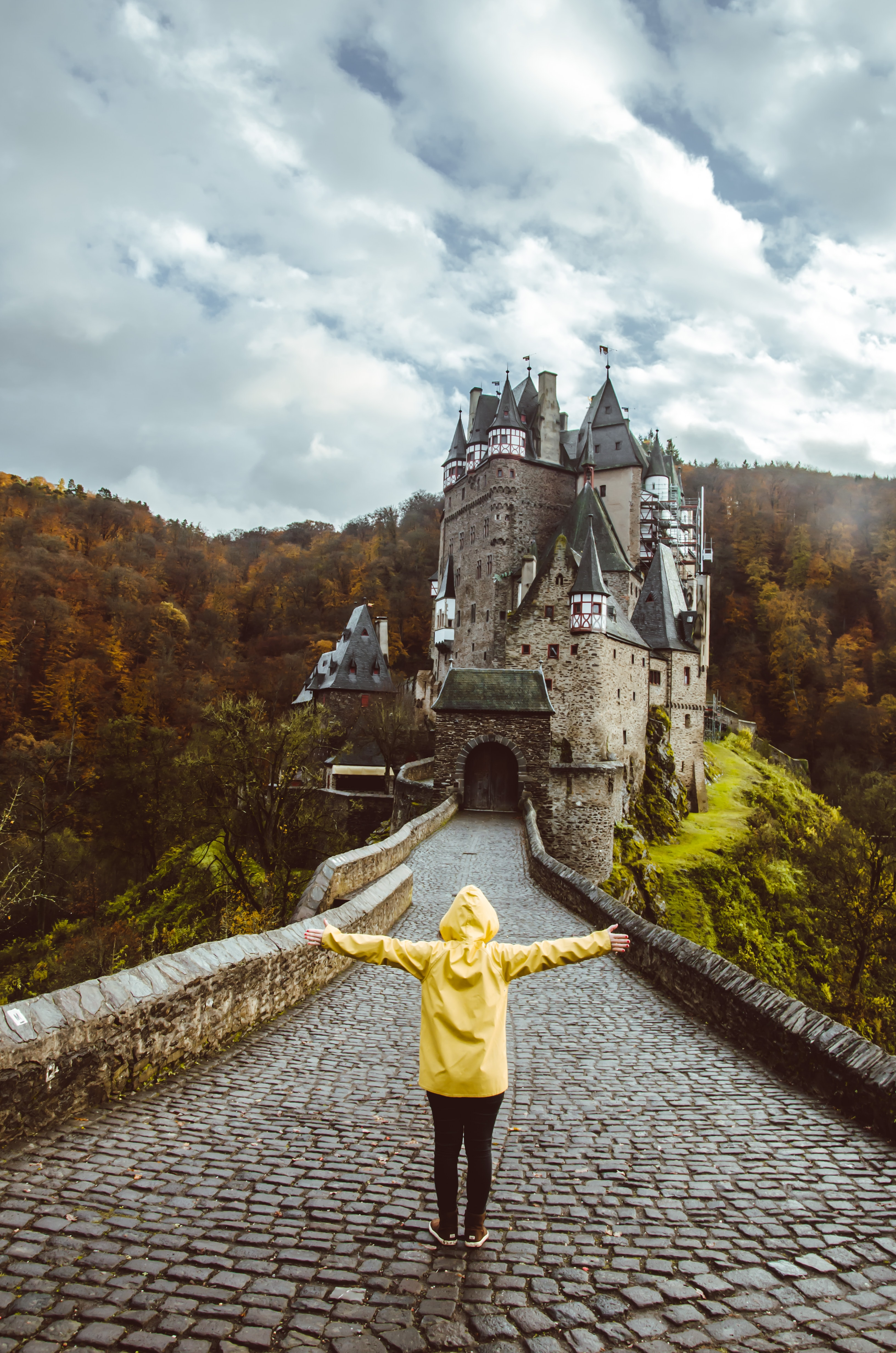 person wearing yellow hoodie standing in front of castle screenshot