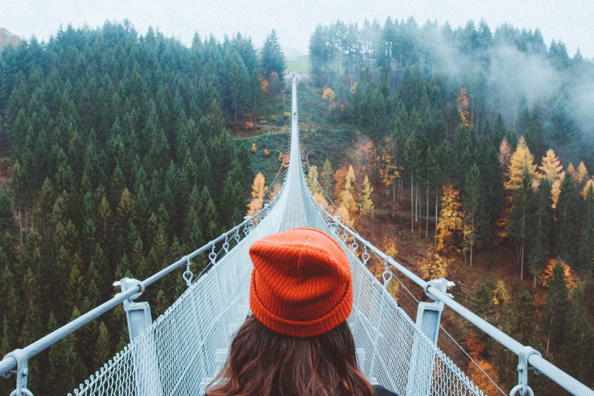 woman wearing knit cap walking on white bridge between trees during daytime