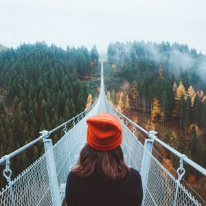 woman wearing knit cap walking on white bridge between trees during daytime