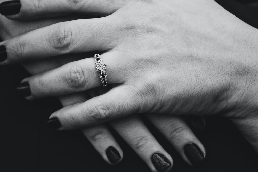 grayscale photography of person wearing ring