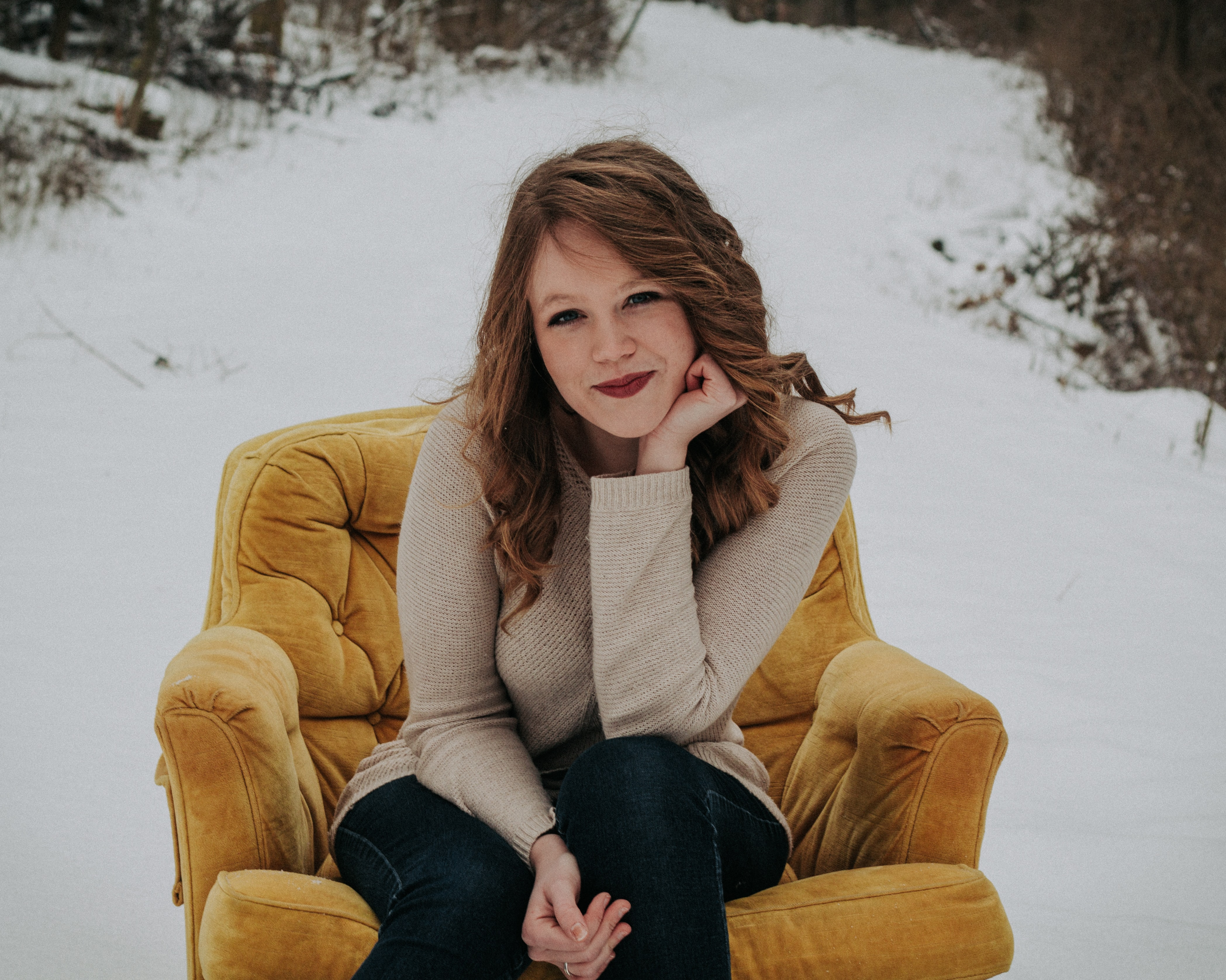woman sitting on sofa chair surrounded with snow and trees