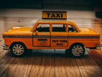 close photography of yellow die-cast taxi model on top of brown wooden furniture