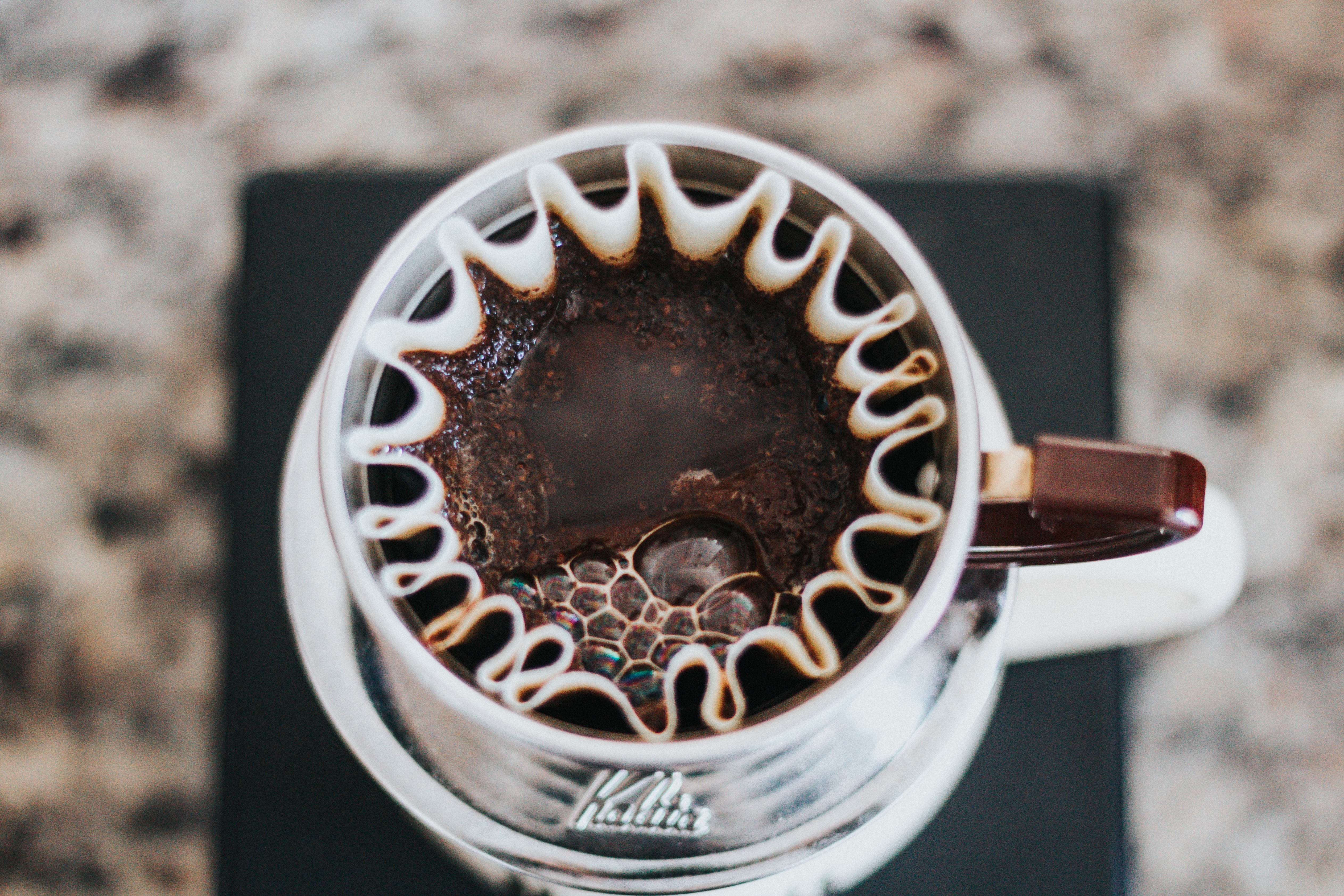 white and brown mug with coffee