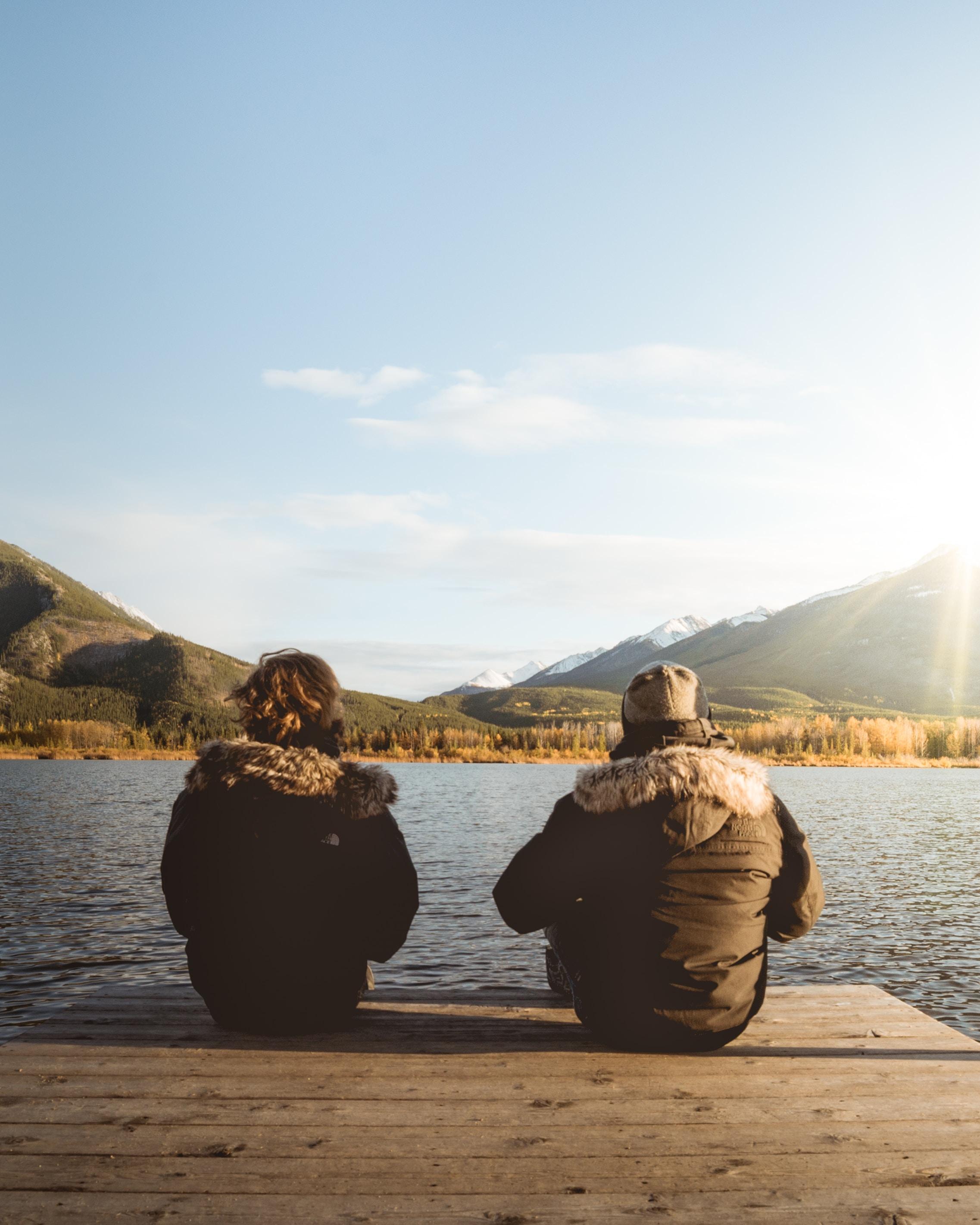 two women sitting on dock at daytime