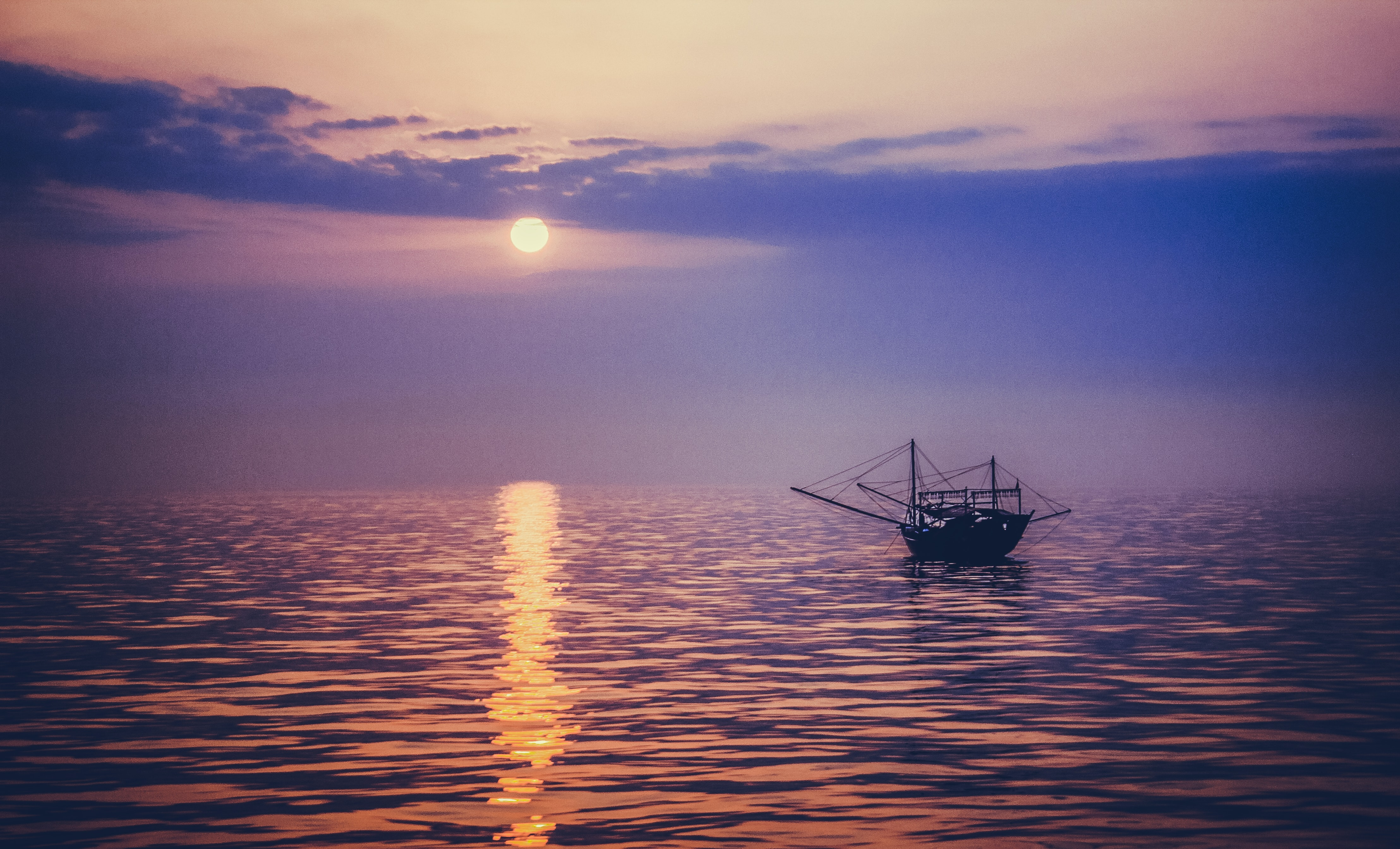 silhouette photo of sailing boat during golden hour